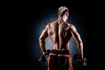 rear view of bodybuilder training with dumbbells on black backgr