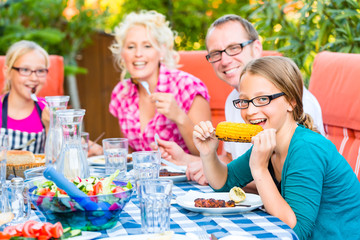 Grillparty bei Familie im Garten vor Haus