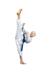 The boy with a blue belt hits a high kick into air