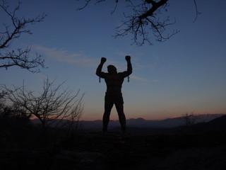 Силуэт человека на фоне синего закатного неба и горных вершин