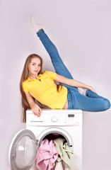 Flexible girl sitting on the washing machine