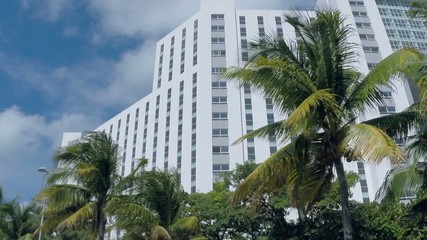 Exterior of multi-story white building with many windows and t