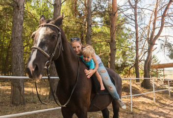Mum with small son drive on horse
