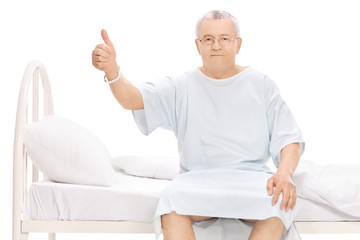 Mature patient sitting on a hospital bed, giving a thumb up
