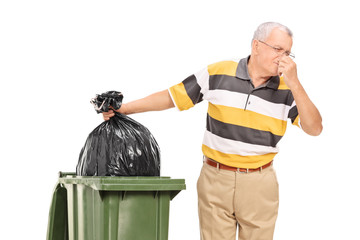 Senior throwing away a stinky bag of trash