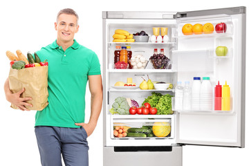 Young man standing by an open refrigerator and holding a grocery