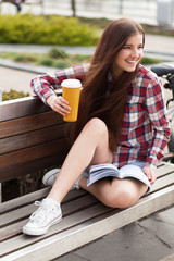 Young woman drinking coffee on a bicycle trip