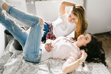 Two young beautiful girls laughing and posing in the bedroom sit