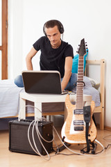 Young man playing electric guitar at home