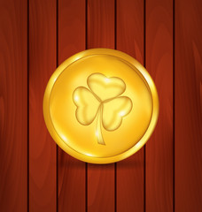 Golden coin with clover on brown wooden texture for St. Patrick'