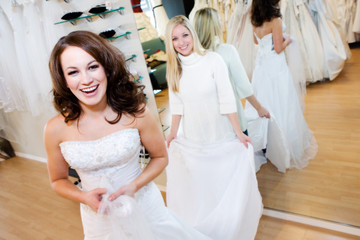 Bride: Woman Trying On Wedding Gown With Help Of Saleswoman