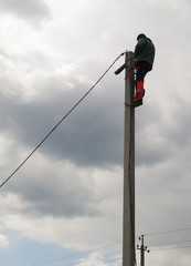 electrician to lay cables on a pole