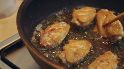 Deep fried chicken with hot oil in pan