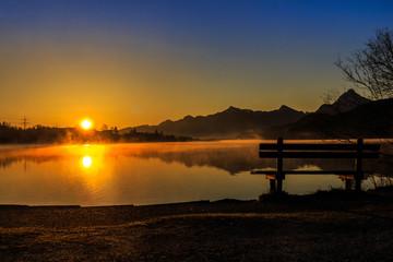 Sonnenaufgang mit Bank am See