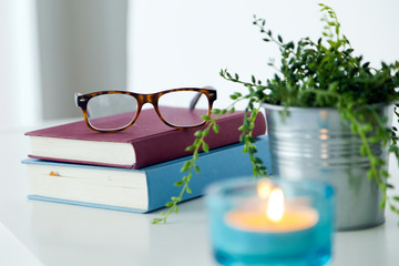 Books, glasses and candle on the night table.