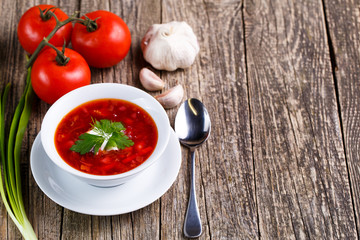 Borsch with bread on a wooden background.