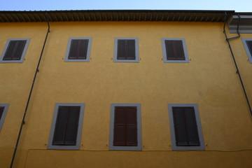 Facciata palazzo giallo con finestre e persiane