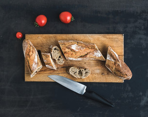 French baguette cut into pieces and cherry-tomatoes on a rustic