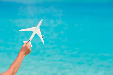 Small white toy airplane on background of turquoise sea