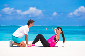 Young couple do abdominal crunches on white beach during