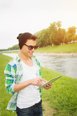 Young hipster man with digital tablet by the river