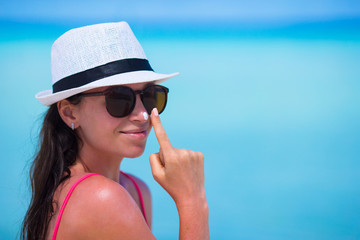 Young happy woman applying suntan lotion on her nose on white
