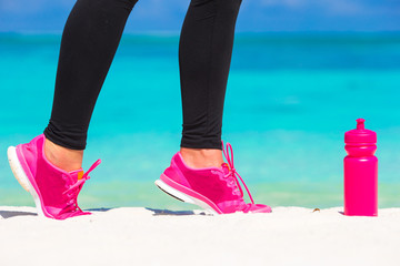 Close-up of female legs in sneakers running on white sandy beach