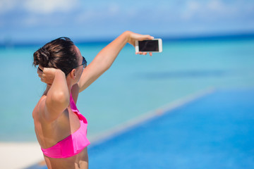 Young beautiful woman taking selfie with phone outdoors during