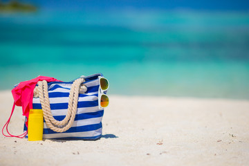 Blue bag, swimsuit, sunglasses and suncream on white beach
