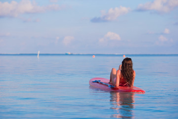 Beautiful surfer woman surfing in turquoise sea during summer
