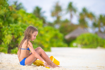 Adorable little girl playing with beach toys during tropical