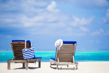 Lounge chairs with bag and hat on tropical beach at Maldives