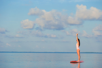 Beautiful young woman surfing on stand up paddle board at exotic