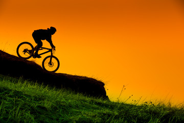 silhouette of downhill mountain bike ride at sunset