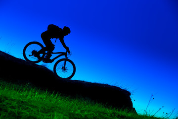 silhouette of downhill mountain bike ride at blue sky