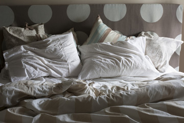 Double bed unmade, with the morning light