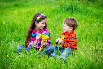 Two kids with dandelions on a meadow