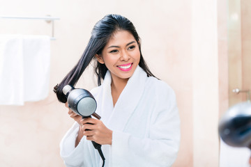 Asian woman in bathroom drying hair
