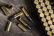Scattering of small caliber cartridges on a wooden background - 81964047