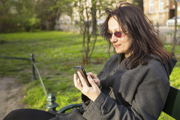 Woman sitting on a park bench speaks by phone.