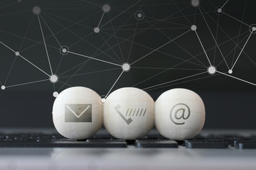 icon on wooden ball of website and internet contact us page conc