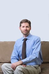 Business man in blue shirt and tie seated on couch
