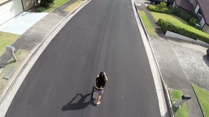 Aerial of young woman riding skateboard on a residential street
