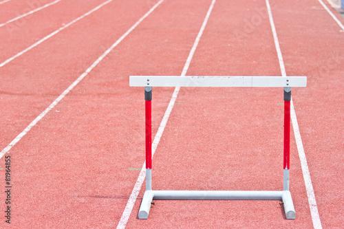 Fototapeta hurdles on the red running track