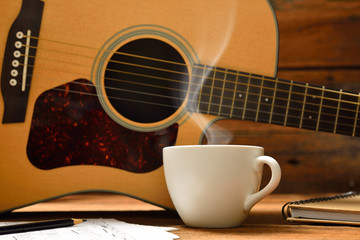 Cup of coffee with smoke and guitar on wooden table © amenic181