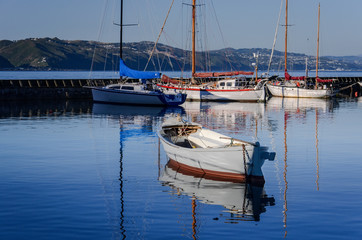 Reflections of boats in the harbor water