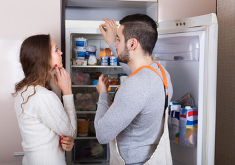 Housewife showing broken refrigerator