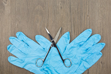 Silver surgical scissors and blue rubber glove