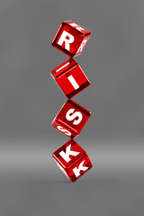 Balancing dice with letters on them spelling the word risk.