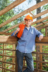 Confident Construction Worker Holding Pipe In Timber Cabin